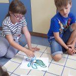 Dziewczynka zakłada ozobotowi przebranie ośmiornicy, chłopiec obserwuje.