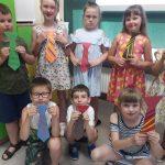 Dzieci przymierzają papierowe krawaty.