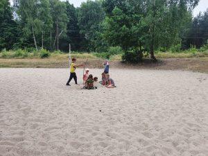 Dzieci bawią się w piasku.