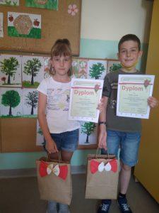 Uczniowie prezentują dyplomy i nagrody (Dorota i Michał z 2b)