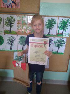 Uczennica prezentuje dyplom i nagrodę (Syntia 2b)