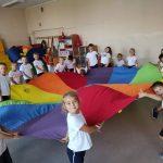 Uczniowie klasy 1 a bawią się kolorową chustą.