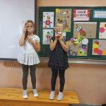 Dwie uczennice w sukienkach w kropki z klasy 1 c stoją na tle prac plastycznych stworzonych z kropek.