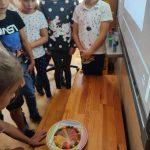 Kilku uczniów z klasy 1 a ogląda barwną tęczę, która powstała z cukierków Skittles.