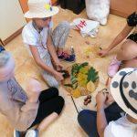 Kilku uczniów z klasy 3 a tworzy jesienną mandalę.