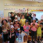 Uczniowie klasy 3 a ubrani w różne czapki w kropki prezentują kolorowe kropki.