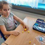 Uczennica buduje z klocków Lego kaczkę.