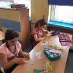Dziewczynki próbują ułożyć kaczuszki z 10 klocków Lego.