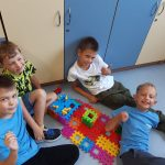 Chłopcy prezentują psią rodzinkę z klocków Lego i ich budy.
