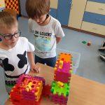 Chłopcy prezentują zbudowane z klocków wafli budy dla psów oraz pieski z Lego.
