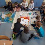 Uczniowie układają drogę dla ozobotów z puzzli.