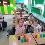 Dzieci kodują i rozkodowują wyrazy z kolorowych kubeczków.