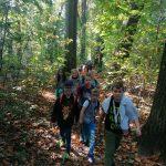 Uczniowie idą starym, leśnym traktem.
